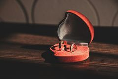 Wedding rings in a red box on a wooden table stock photography
