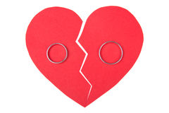 Wedding rings on red broken heart isolated on white Royalty Free Stock Photography