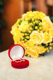 Wedding rings in a red case. Wedding rings in the red case on a background of yellow bride's bouquet Royalty Free Stock Photos