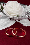 Wedding rings on a red cloth. Against the background of a flower Royalty Free Stock Photography