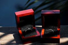 Wedding rings in red glossy box on wooden background with spot of sun light royalty free stock image