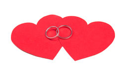 Wedding rings on red heart isolated on white Royalty Free Stock Photo