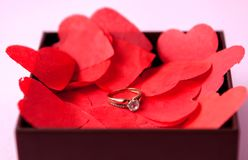 Wedding rings on the red hearts. Pink background. The concept of betrothal, divorce, parting, infidelity .Selective focus.  stock images