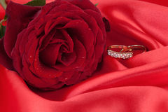 Wedding Rings with red Rose on a Red Silk Royalty Free Stock Photography