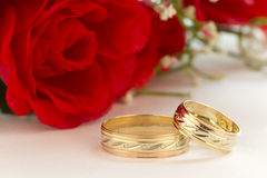 Wedding rings with red roses. Close up to the wedding rings with bouquet of red roses on a white background Stock Photo