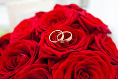 Wedding rings on red roses Royalty Free Stock Photo