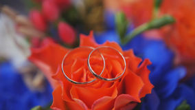 Wedding rings on red roses bouquet, close up stock photography