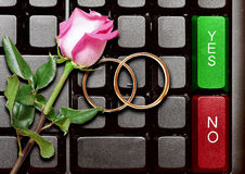 Wedding rings and red roses on computer keyboard Royalty Free Stock Images