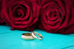 Wedding rings and red roses. Wedding bouquet on blue wooden background. Selective focus. Copy space. Wedding rings and red roses. Wedding bouquet on blue wooden Stock Image