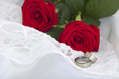Wedding rings and red roses on white lace and silk Stock Photo