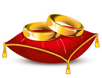 Wedding rings on red satin pillow. Gold wedding rings on red satin pillow with tassels Stock Photography