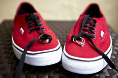 Wedding rings on red sneakers Stock Photos