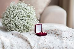 Wedding rings in a red velvet box and a bridal bouquet over a white lace wedding dress. Selective , copy space stock photography