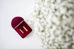 Wedding rings in a red velvet box and a bridal bouquet over a white table - flat lay top-down composition. Wedding rings in a red velvet box and bridal bouquet royalty free stock photography