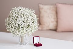Wedding rings in a red velvet box and a bridal bouquet over a white table. Wedding rings in a red velvet box and bridal bouquet over a white table - selective royalty free stock photography