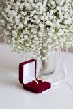Wedding rings in a red velvet box and a bridal bouquet over a white table. Wedding rings in a red velvet box and bridal bouquet over a white table - selective stock photo