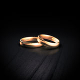 Wedding rings. Rendered image of two golden wedding rings on a dark background Stock Photography