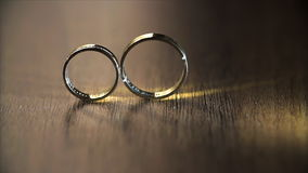 Wedding Rings Rolling. Beautiful wedding rings on a wooden table stock footage