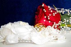 Wedding Rings and Rose-4. Beautiful engagement and wedding rings on top of white lace and red rose sit in front of a blue cloth background.  Valentines Special Stock Images