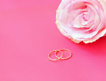 Wedding rings with rose. On a pink background Stock Photo