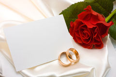 Wedding rings, rose and card. Two gold wedding rings, red rose and card over white satin Royalty Free Stock Photos