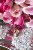 Wedding rings in rose. Detail of a bouquet of roses and wedding rings Royalty Free Stock Photo