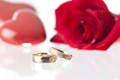 Wedding rings and rose.GN. Wedding rings with a red rose and laying on a glass surface.GN stock images