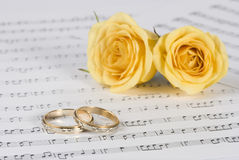 Wedding rings and roses. With musical sheet background royalty free stock image