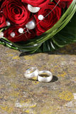 Wedding rings with roses. Still-life with wedding rings and red roses Royalty Free Stock Images