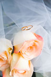 Wedding rings and roses. Couple wedding rings with veil on bouquet of roses stock image