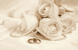 Wedding rings and roses as wedding background. In Sepia toned. R Stock Photo