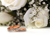 Wedding rings and roses bouquet Stock Images