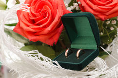 Wedding rings and roses bouquet Stock Image