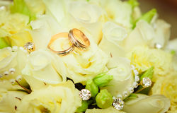 Wedding rings and roses bouquet Royalty Free Stock Photography