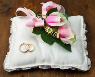 Wedding rings with roses on bridal pillow Stock Image