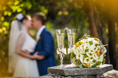 Wedding rings with roses and glasses of champagne and a kiss of the groom and bride Stock Photo