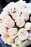 Wedding rings and roses. Two wedding rings lie on a bouquet of light pink roses.  Rings are golden Royalty Free Stock Photography