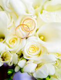 Wedding rings and roses. Two wedding rings lie on a bouquet of light pink roses.  Rings are golden Stock Images