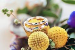 Wedding rings round yellow flowers Royalty Free Stock Photo