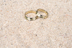 Wedding rings in the sand. A pair of gold wedding rings delicately placed in the sand on a tropical beach Royalty Free Stock Image