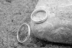 Wedding Rings on the Sand. A pair of wedding rings laying on the sandy ground Stock Photo
