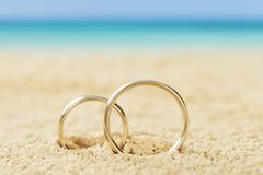 Wedding rings on sand. Photos of wedding rings on sand at beach Royalty Free Stock Image