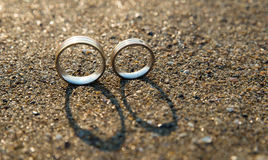 Wedding Rings. In Sand with shadows Royalty Free Stock Images