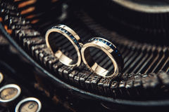Wedding rings with sapphires on a vintage typewriter Royalty Free Stock Photo
