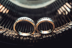 Wedding rings with sapphires on a vintage typewriter Royalty Free Stock Photos