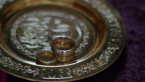 Wedding rings on a saucer in the church. stock video footage
