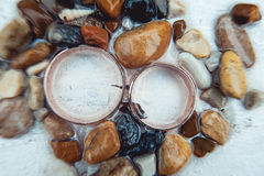 Wedding rings in the sea pebbles on a white background Stock Photos
