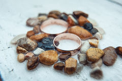 Wedding rings in the sea pebbles on a white background Stock Photo