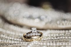Wedding rings on sequins and pearls Stock Images