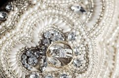 Wedding rings on sequins and pearls Stock Photo